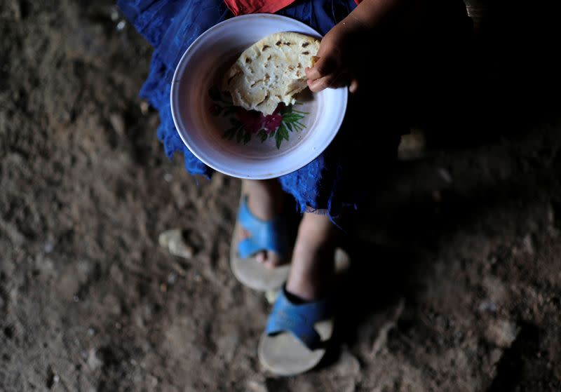 Claudia Faviola Gonzales, a three-year-old girl, eats a tortilla with salt at her home, in La Palmilla