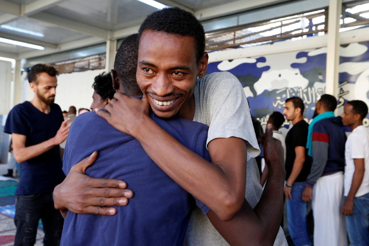 Muslim migrants exchange greetings after Eid al-Fitr prayers to mark the end of the holy fasting month of Ramadan at a detention centre in Tripoli, Libya June 15, 2018. REUTERS/Ismail Zitouny