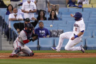 Los Angeles Dodgers' AJ Pollock, right, scores on a single by Zach McKinstry as Washington Nationals catcher Yan Gomes can't hold on to the throw during the second inning of a baseball game Saturday, April 10, 2021, in Los Angeles. (AP Photo/Mark J. Terrill)