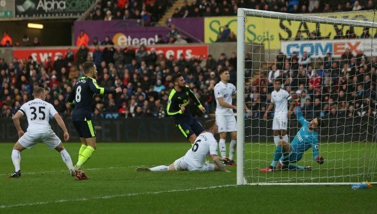 Arsenal's in-form French striker Olivier Giroud (C) scores his team's first goal against Swansea City