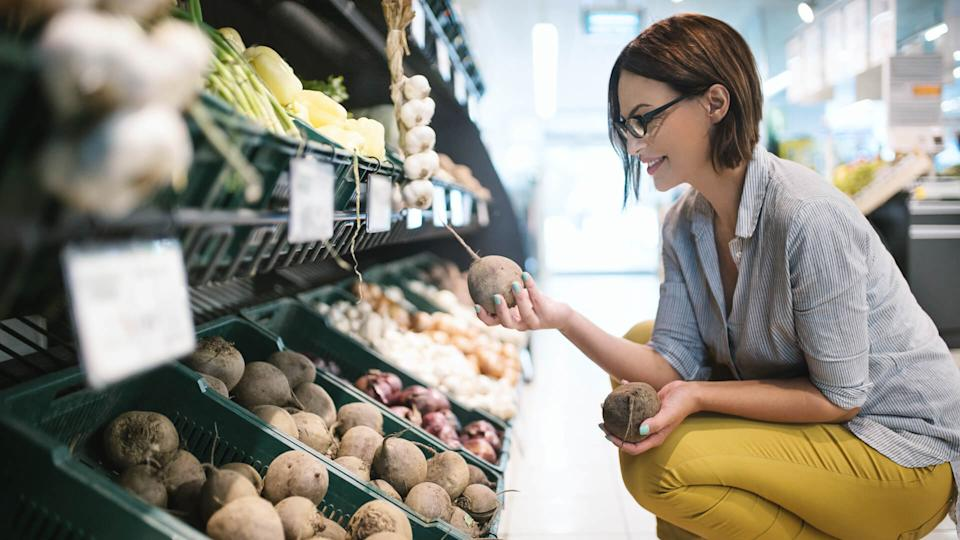 Attractive brunette woman choosing lettuce to buy in a supermarket.