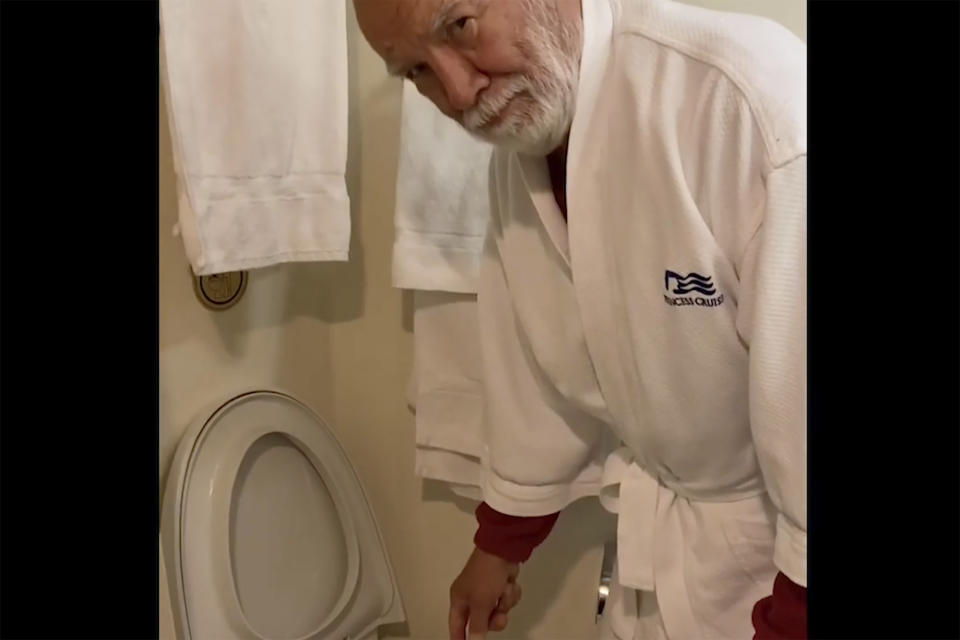 In this image from a video taken on Feb. 10, 2020, Paul Molesky scrubs the toilet in his cabin on the Diamond Princess, anchored at a port in Yokohama, near Tokyo. Even during the quarantine, it can seem like Cheryl and Paul Molesky are still on vacation. (Cheryl and Paul Molesky via AP)