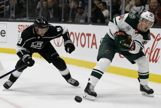 Minnesota Wild defenseman Nick Seeler, right, clears the puck away from Los Angeles Kings center Adrian Kempe, left, of Sweden, during the second period of an NHL hockey game in Los Angeles, Thursday, Nov. 8, 2018. (AP Photo/Alex Gallardo)