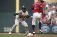 Minnesota Twins' Ehire Adrianza, right, is tagged out at first base by Oakland Athletics second baseman Jurickson Profar on Adrianza's sacrifice bunt during the third inning of a baseball game Thursday, July 18, 2019, in Minneapolis. (AP Photo/Jim Mone)