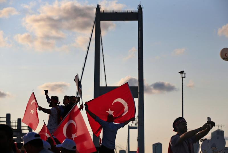 "People wave Turkish flags near the July 15 Martyr's bridge on a ""National Unity March - Credit: Lefteris Pitarakis/AP"