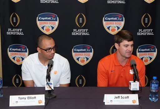 FILE - In this Dec. 27, 2015, file photo, Clemson co-offensive coordinators Tony Elliott, left, and Jeff Scott speak to the media at a news conference in Fort Lauderdale, Fla. Despite helping Clemson win a national title as co-offensive coordinator, Elliott has never interviewed for a head-coaching job. College football as a public entity cant institute a Rooney Rule like the NFL to compel programs to interview minority candidates for head coaching jobs. So the NCAA is trying to do the next best thing by putting some of the rising coaching stars through its Champion Forum that better prepares them for the interview process in an effort to increase the diversity in the Power Five conferences and across the country. (AP Photo/Gaston De Cardenas, File)