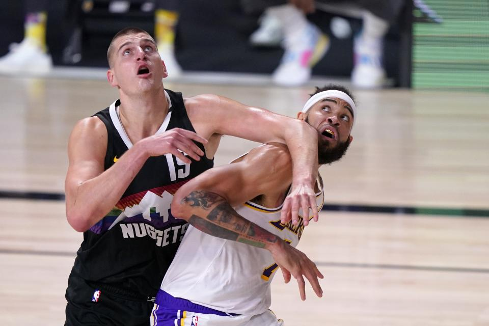 Denver Nuggets' Nikola Jokic (15) and Los Angeles Lakers' JaVale McGee, right, compete for a rebound during the first half of Game 3 of the NBA basketball Western Conference final Tuesday, Sept. 22, 2020, in Lake Buena Vista, Fla. (AP Photo/Mark J. Terrill)