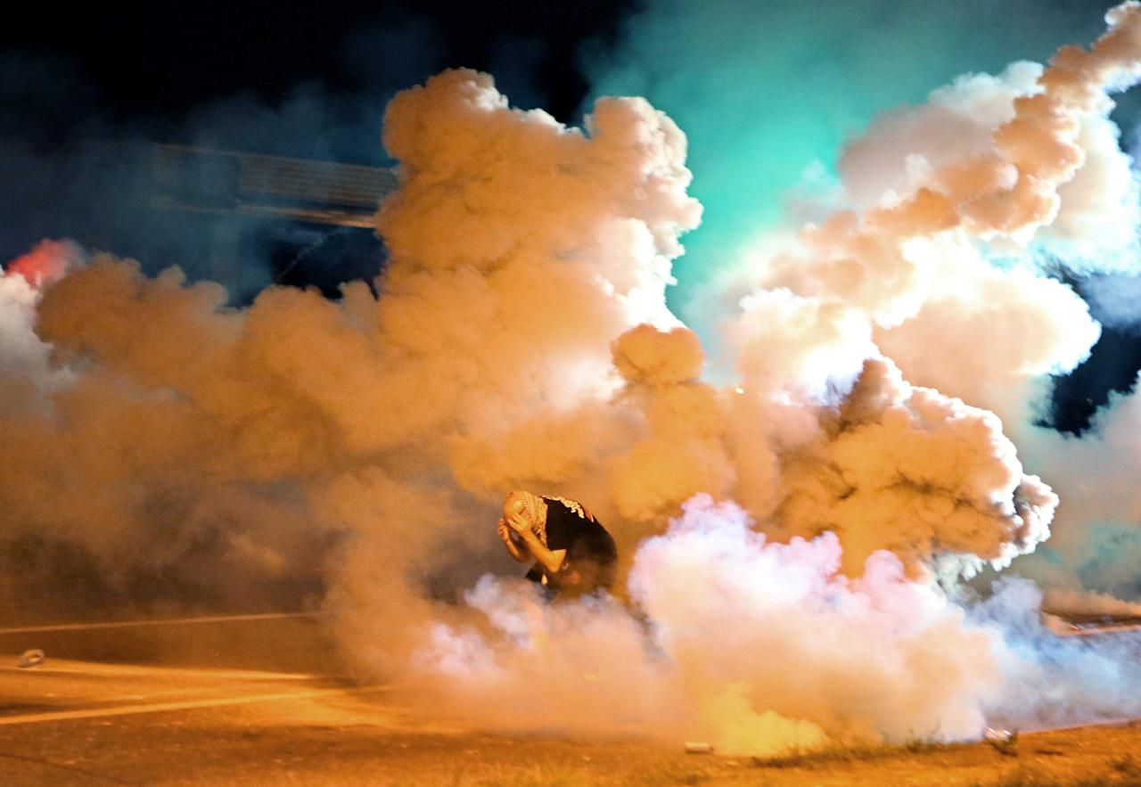 <p>Aug 13, 2014 – Ferguson, Missouri, U.S. – A protester takes shelter from tear gas canisters exploding around him on West Florissant Ave. On this night protesters attempted to throw Molotov cocktails, rocks and bottles at police. This was the four straight night police used tear gas to disperse crowds protesting the death of Michael Brown. (David Carson/St Louis Post-Dispatch/ZUMAPRESS.com) </p>