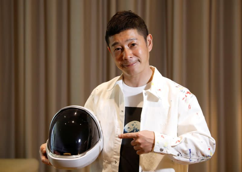Japanese billionaire Yusaku Maezawa poses with a space suit helmet during an interview with Reuters in Tokyoo
