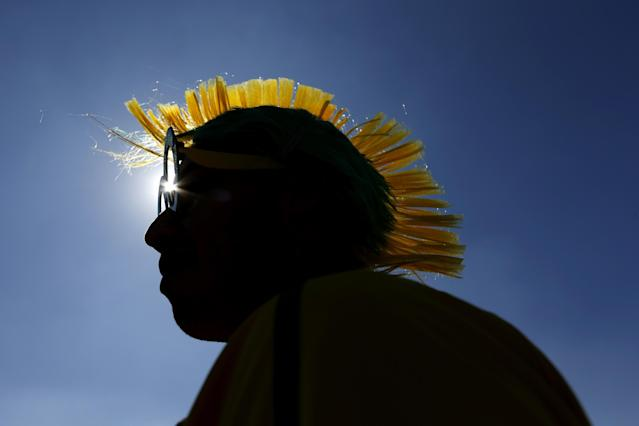"Brazilian Marcelo Bora, 22, and his mohawk-styled wig, are silhouetted against a blue sky as he waits to enter the Itaquerao Stadium to watch the World Cup opening match, between Brazil and Croatia of group A, in Sao Paulo, Brazil, Thursday, June 12, 2014. Thursday is a holiday in Sao Paulo and everybody is celebrating the start of the international soccer tournament. Fans dressed in yellow and green greeted each other, often yelling, ""Vai Brazil!"" (AP Photo/Julio Cortez)"