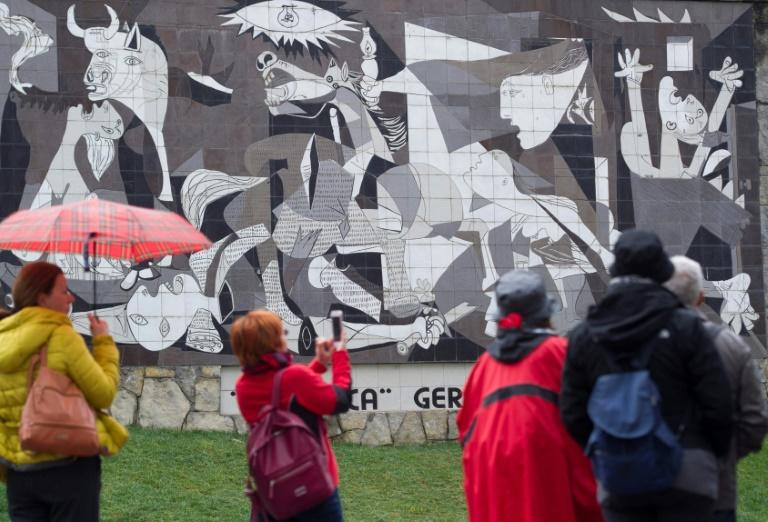 "Tourists take pictures of a mural depicting Pablo Picasso's painting ""Guernica"" in the northern Spanish town on the 80th aniversary of a  Nazi bombing raid that killed hundreds"