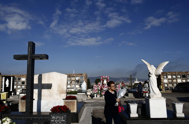 <p>A woman places flowers in a grave during All Saints' Day, a Catholic holiday to reflect on the saints and deceased relatives, at the Montjuic cemetery in Barcelona, Spain, Wednesday, Nov. 1, 2017. (Photo: Manu Fernandez/AP) </p>