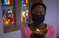 A worshipper wearing a face mask, holds a lit candle prior to a morning Christmas Mass at the Rosebank Catholic Church in Johannesburg, Friday, Dec. 25, 2020. (AP Photo/Denis Farrell)