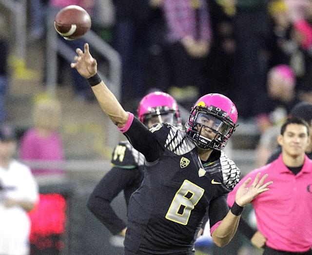 Oregon quarterback Marcus Mariota wears a pink helmet as he warms up before an NCAA college football game against Washington State in Eugene, Ore., Saturday, Oct. 19, 2013. (AP Photo/Don Ryan)