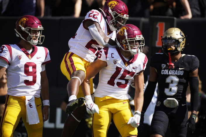 Southern California quarterback Kedon Slovis, left, running back Darwin Barlow and wide receiver Drake London (15) celebrate after London's touchdown catch as Colorado cornerback Christian Gonzalez looks on in the first half of an NCAA college football game Saturday, Oct. 2, 2021, in Boulder, Colo. (AP Photo/David Zalubowski)