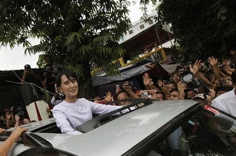 In this Monday, April 2, 2012 photo, Myanmar's opposition leader Aung San Suu Kyi acknowledges supporters from her vehicle as she leaves the headquarters of her National League for Democracy party in Yangon, Myanmar. In very different ways, Myanmar, run by a cabal of generals, and North Korea, run by the same family as a Stalinist dictatorship since the 1940s, have opened themselves up over the past year or so, allowing the world to peer behind the political curtains they had so laboriously erected, but the question of whether there has been any real change still remains. (AP Photo)