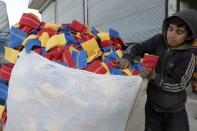 Mohammed Abu Rdan puts dishcloths in a bag, in front of the cleaning products factory, northern Aleppo