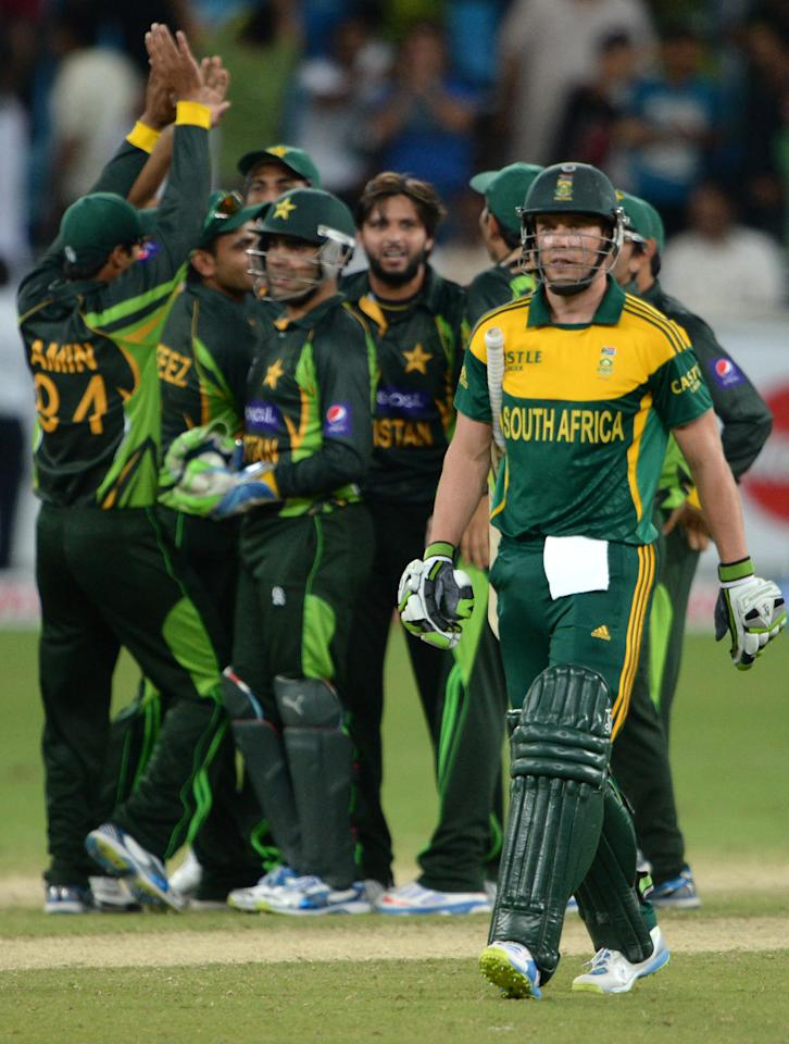 South African captain AB de Villiers (R) leaves the field after being caught  as Pakistani cricketers celebrates during the second day-night international against South Africa in Dubai Cricket Stadium in Dubai on November 1, 2013. Pakistan were bowled out for 209 in their innings. South Africa lead the five-match series 1-0. AFP PHOTO/ Asif HASSAN        (Photo credit should read ASIF HASSAN/AFP/Getty Images)