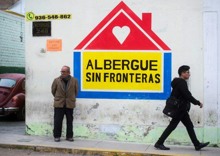 "People walk past the ""Without Borders"" migrant shelter, in northern Lima on August 31, 2018"