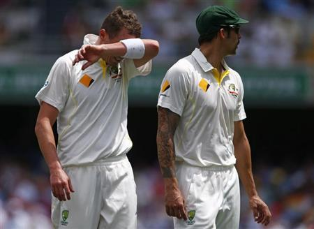 Australia's Peter Siddle (L) reacts next to teammate Mitchell Johnson after dropping a catch played by England's Kevin Pietersen during the second day's play of the first Ashes cricket test match in Brisbane November 22, 2013. REUTERS/David Gray