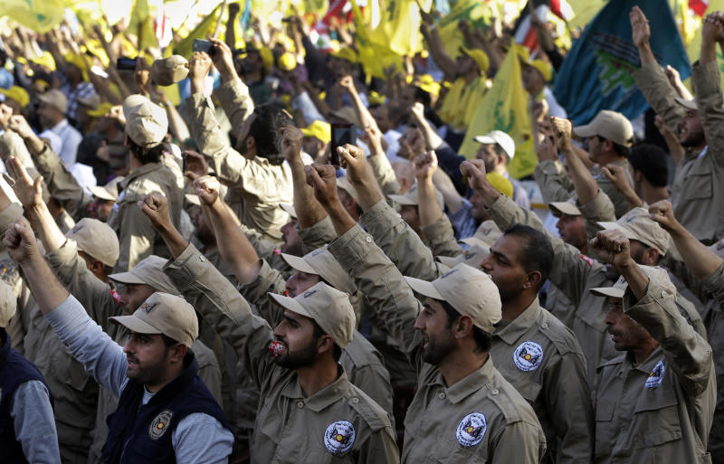 """Members of the demining unit of Hezbollah, raise up their hands as they shout slogans in support of pro-Hezbollah leader Sheik Hassan Nasrallah, during a rally commemorating """"Liberation Day,"""" which marks the withdrawal of the Israeli army from southern Lebanon in 2000, in Mashghara village Bekaa valley, Lebanon, Saturday May 25, 2013. Nasrallah says his Shiite militant group will not stand idly by while its chief ally Syria is under attack. Nasrallah says Hezbollah members are fighting in Syria against Islamic extremists who pose a danger to Lebanon, publicly confirming for the first time that his men were fighting in Syria. (AP Photo/Hussein Malla)"""