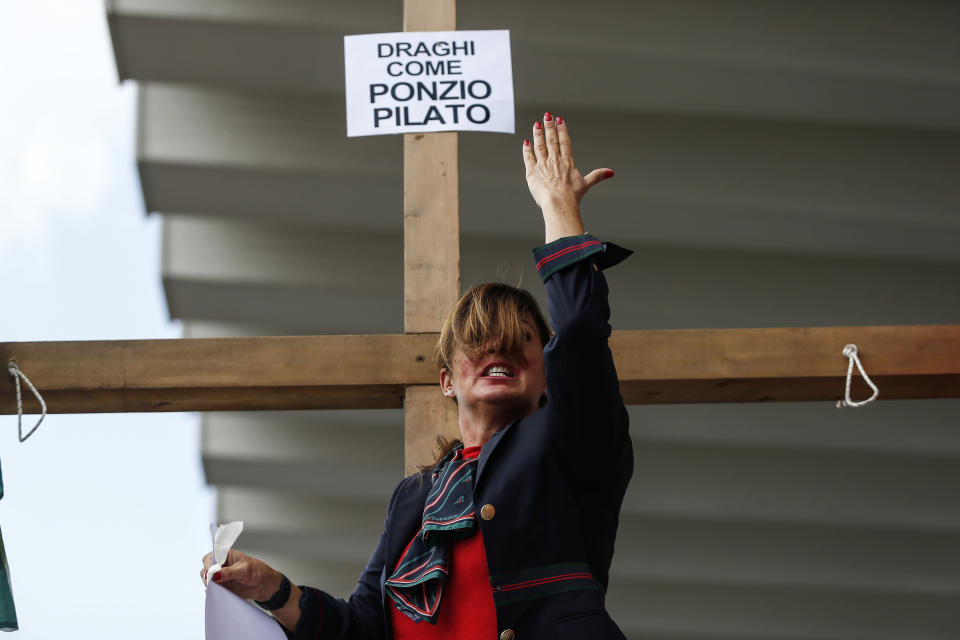 """A woman stands by a cross with a note reading in Italian """"Draghi like Pontius Pilates"""" as Alitalia workers stage a protest at the Rome Leonardo Da Vinci international airport in Fiumicino, Friday, Sept. 24, 2021. Alitalia, which has been in the red for more than a decade, is due to formally exit the airline market next month and be replaced by a new national carrier ITA, or Italy Air Transport. The European Commission has given the go-ahead to a 1.35 billion euro ($1.58 billion) injection of government funding into the new airline, but ITA is only planning to hire around a quarter of the estimated 10,000 Alitalia employees.(Cecilia Fabiano/LaPresse via AP)"""