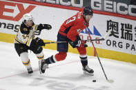 Washington Capitals right wing Tom Wilson (43) skates with the puck past Boston Bruins defenseman Jack Ahcan (54) during the second period of an NHL hockey game, Tuesday, May 11, 2021, in Washington. (AP Photo/Nick Wass)