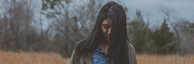 Young woman outside in a field wearing a denim shirt and jacket looking at the ground with her face partially covered by long brown hair