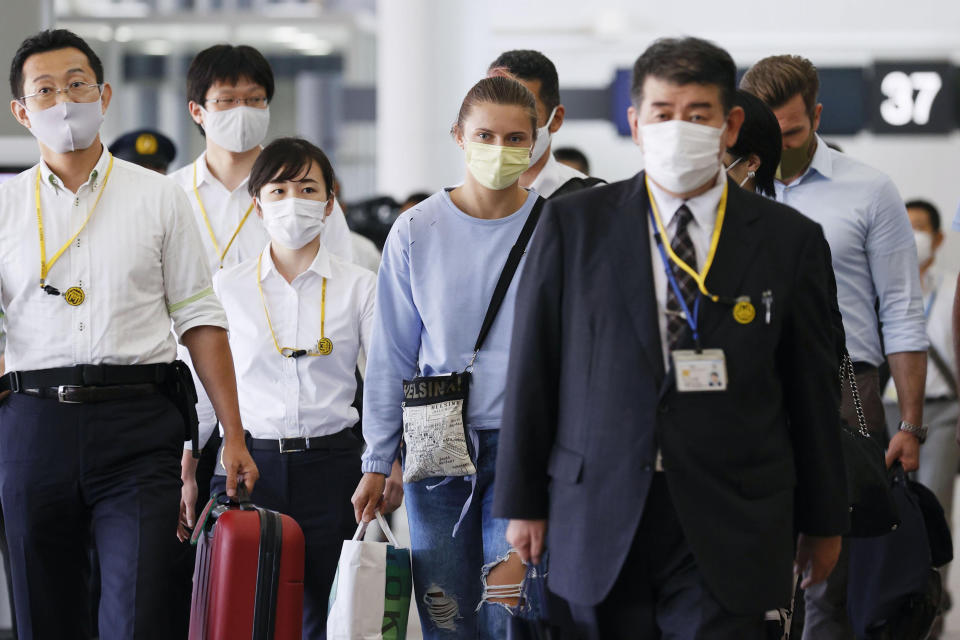 Belarusian Olympic sprinter Krystsina Tsimanouskaya, center, prepares to leave Narita International Airport in Narita, east of Tokyo Wednesday, Aug. 4, 2021. Tsimanouskaya, who plans to seek refuge in Europe, boarded a plane that left the gate for Vienna on Wednesday morning, though it was not immediately clear if that would be her final destination. (Kyodo News via AP)