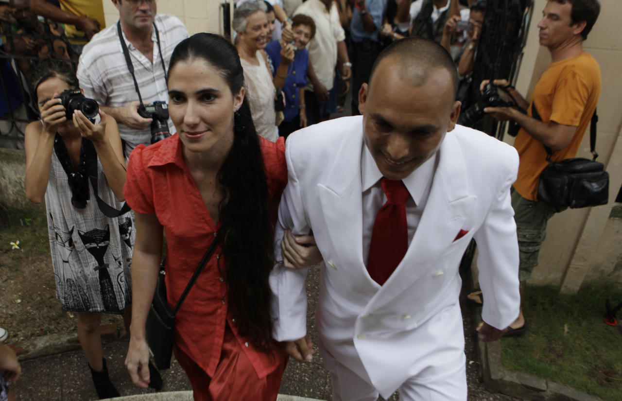 Groom Ignacio Estrada and maid of honor, Cuba's blogger Yoani Sanchez, arrive for his wedding in Havana, Cuba, Saturday Aug. 13, 2011. Transsexual Wendy Iriepa, whose sex change operation was paid for by the state, tied the knot with Estrada in a first-of-its-kind wedding for Cuba. Gay marriage is not legal in Cuba and Saturday's wedding does nothing to change that since Iriepa is legally considered a woman. (AP Photo/Javier Galeano)