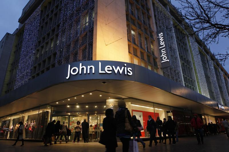 Shoppers pass in front of John Lewis department store in Oxford Street in central London