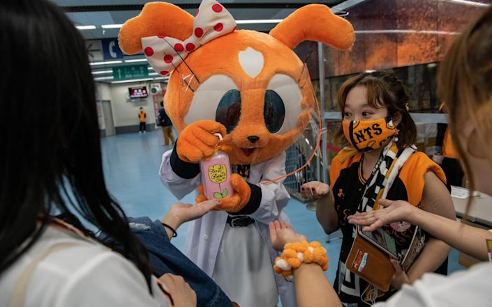 A Yomiuri Giants mascot wearing a plastic visor sprays hand sanitiser onto the hands of fans at Tokyo Dome ahead of the Japan Central League baseball match - Getty