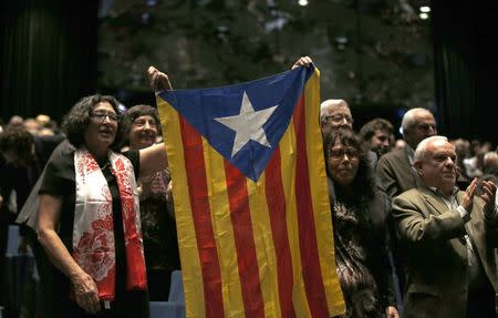 Supporters hold up a Catalan independence flag during a conference in Barcelona