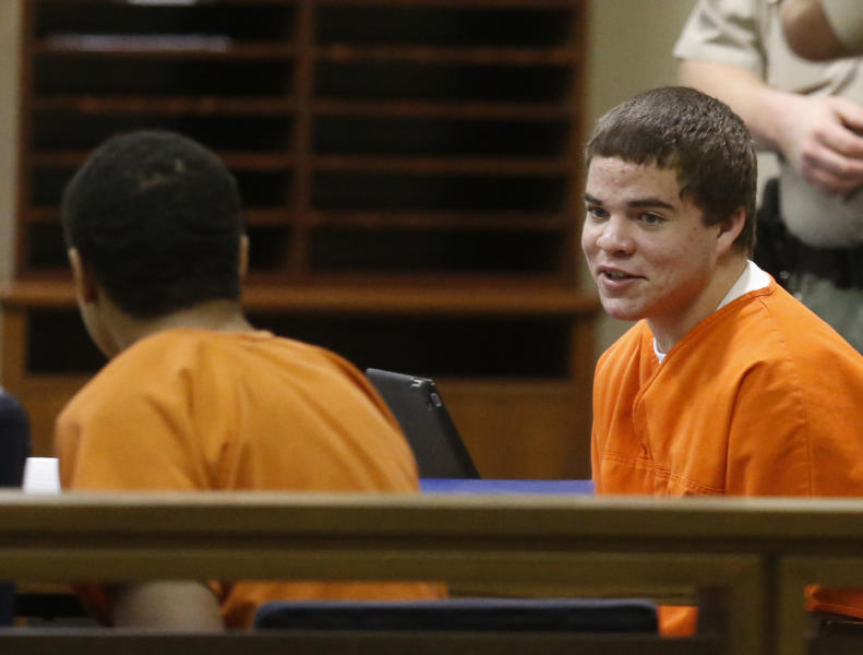 In this photo shot through a courtroom door, defendants Michael Jones, right, and Chancey Luna, left, talk in the courtroom following a hearing in Duncan, Okla, Wednesday, March 12, 2014. An Oklahoma judge ruled that the two teenagers charged with first-degree murder must face a trial in the shooting death of an Australian baseball player, Christopher Lane. (AP Photo/Sue Ogrocki)