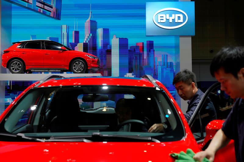FILE PHOTO: Men clean a BYD electric vehicle (EV) e2 displayed during the media day for Shanghai auto show