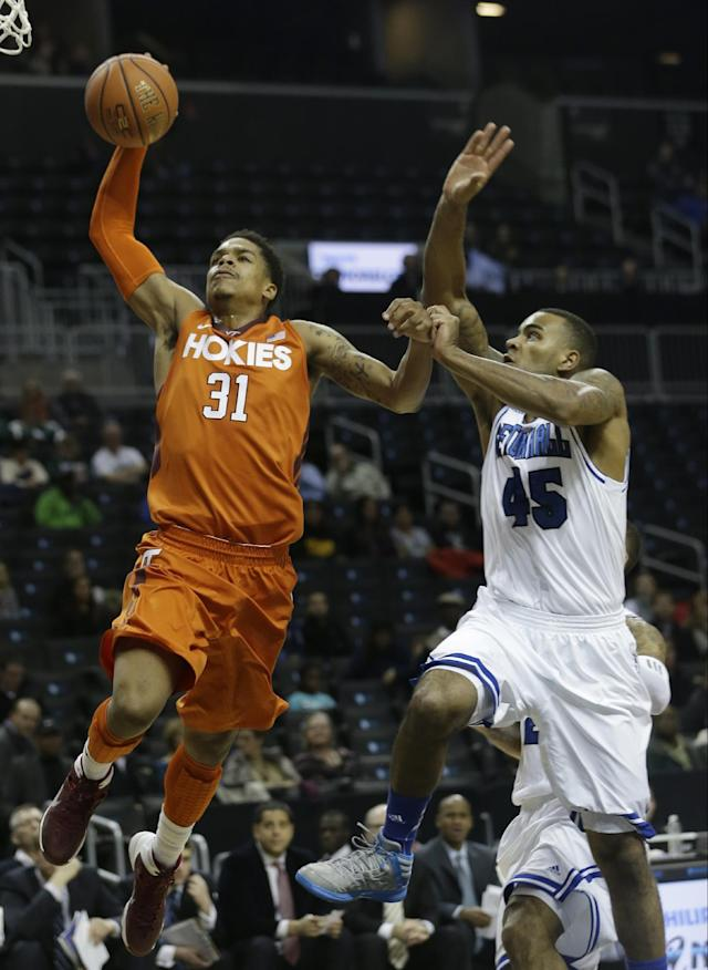 Virginia Tech's Jarell Eddie (31) drives past Seton Hall's Stephane Manga (45) during the first half of a consolation game in the Coaches vs. Cancer NCAA college basketball game on Saturday, Nov. 23, 2013, in New York. Manga blocked the shot on the play. (AP Photo/Frank Franklin II)