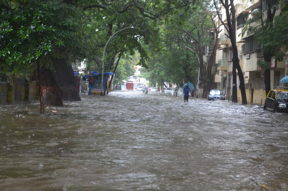 Commuters brave a flooded road in Mumbai. (Photo by Arun Patil)