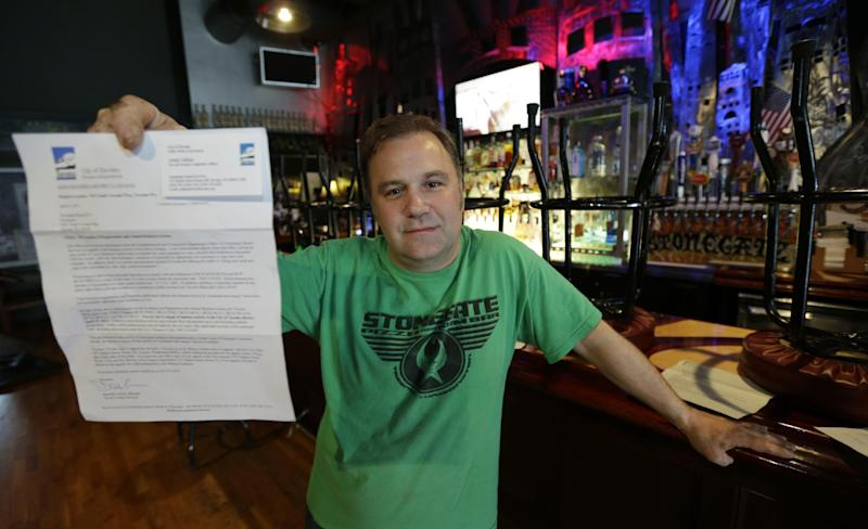 Jeff Call, owner of the Stonegate Pizza and Rum Bar in Tacoma, Wash., poses for a photo Thursday, April 18, 2013 with a letter he received from the city of Tacoma revoking Call's business license because he allows customers to use vaporized marijuana upstairs in a private club area of his bar. Call filed an appeal Thursday and will continue operating his business. (AP Photo/Ted S. Warren)