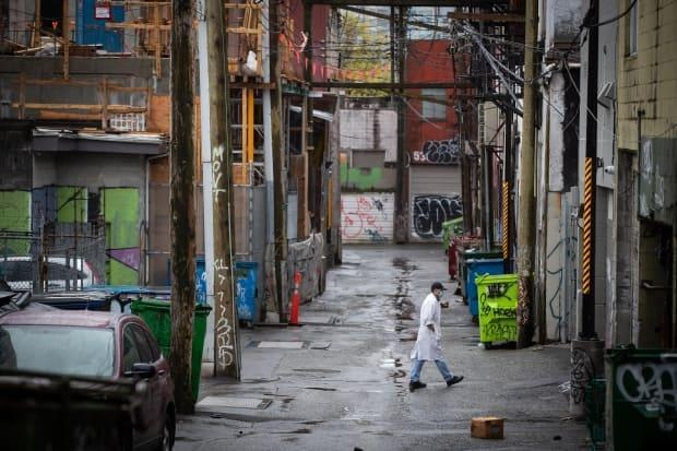 A man wearing a face mask to curb the spread of COVID-19 walks through an alley in Chinatown, in Vancouver, on Sunday, April 25, 2021.  (Darryl Dyck/Canadian Press - image credit)