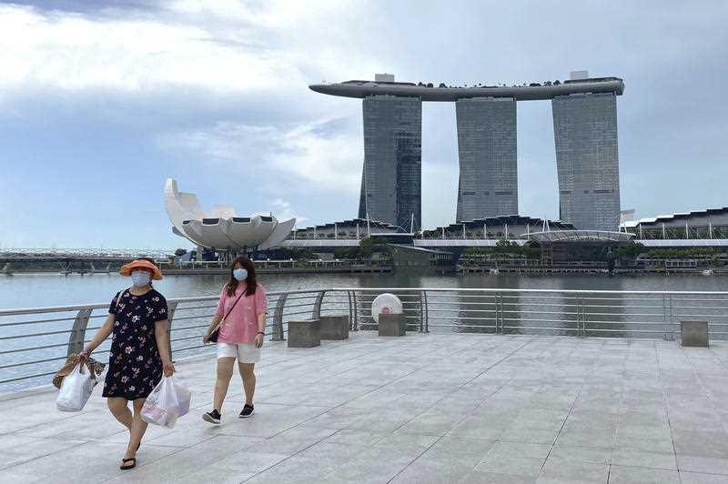 Visitors wear masks while walking around Merlion Park, a popular tourist destination, with the Marina Bay Sands in the background in Singapore.