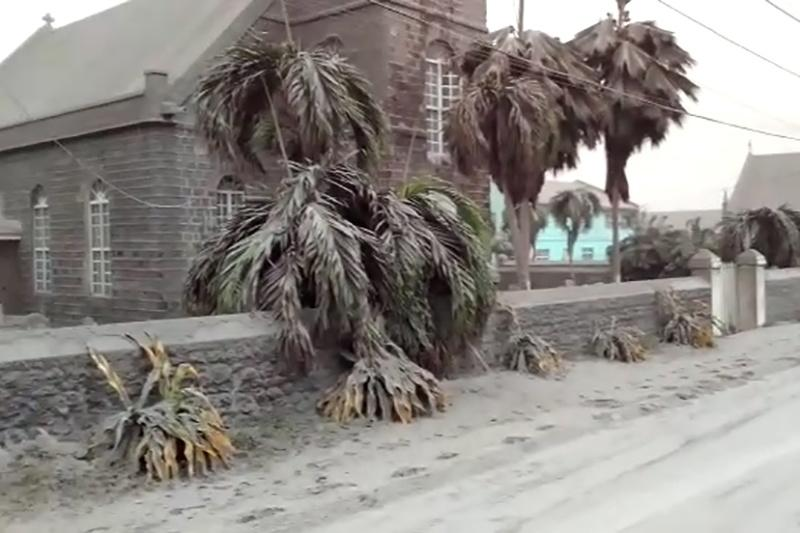 Ash covers palm trees and a church a day after the La Soufriere volcano erupted after decades of inactivity, about 5 miles (8 km) away in Georgetown, St Vincent and the Grenadines April 10, 2021 in a still image from video.  REUTERS/Robertson S. Henry