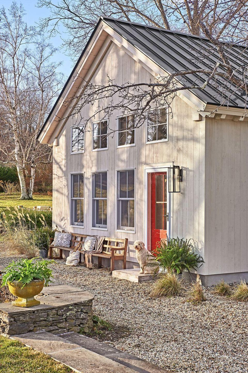 """<p>Red is always an easy way to bring attention to your front door. Try a bright shade against neutrals, like this clapboard siding and metal roof.</p><p><a class=""""link rapid-noclick-resp"""" href=""""https://go.redirectingat.com?id=74968X1596630&url=https%3A%2F%2Fwww.homedepot.com%2Fp%2FRust-Oleum-Painter-s-Touch-32-oz-Ultra-Cover-Gloss-Apple-Red-General-Purpose-Paint-1966502%2F100209277&sref=https%3A%2F%2Fwww.countryliving.com%2Fhome-design%2Fcolor%2Fg31158913%2Ffront-door-colors%2F"""" rel=""""nofollow noopener"""" target=""""_blank"""" data-ylk=""""slk:SHOP RED PAINT"""">SHOP RED PAINT</a></p>"""
