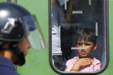 A migrant boy looks at a Hungarian policeman at the railway station in the town of Bicske