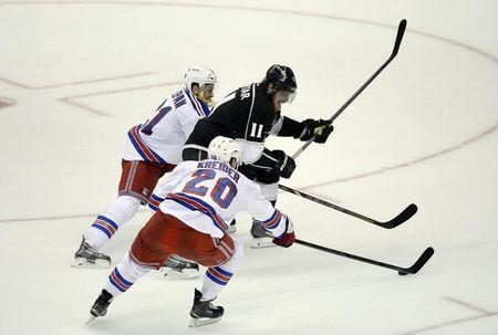 Los Angeles Kings center Anze Kopitar (11) battles for the puck between New York Rangers center Derek Stepan (21) and left wing Chris Kreider (20) during the second period in game five of the 2014 Stanley Cup Final at Staples Center. Jun 13, 2014; Los Angeles, CA, USA; Richard Mackson-USA TODAY Sports
