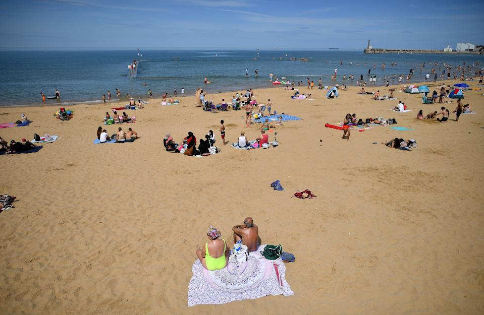 "People enjoy the sunshine on the beach and in the sea in Margate, south east England on May 26, 2020, after some lockdown restrictions put in place to slow the spread of COVID-19 were partially eased earlier this month. - Britain's number of deaths ""involving"" the coronavirus has risen to 46,000, substantially higher than the 36,914 fatalities officially reported so far, according to a statistical update released Tuesday. The daily death tolls released in Britain only include fatalities that have been confirmed by a positive test. (Photo by Ben STANSALL / AFP) (Photo by BEN STANSALL/AFP via Getty Images)"