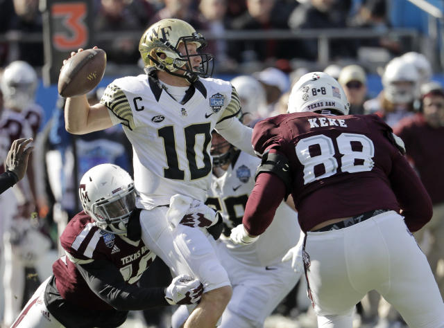 Wake Forest's John Wolford (10) looks to pass under pressure from against Texas A&M's Kingsley Keke (88) during the first half of the Belk Bowl NCAA college football game in Charlotte, N.C., Friday, Dec. 29, 2017. (AP Photo/Chuck Burton)