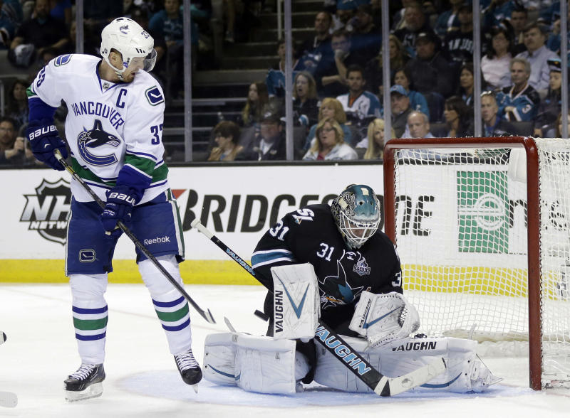 San Jose Sharks goalie Antti Niemi, right, of Finland, stops as shot next to Vancouver Canucks center Henrik Sedin, of Sweden, during the second period of Game 3 of their first-round NHL hockey Stanley Cup playoff series in San Jose, Calif., Sunday, May 5, 2013. (AP Photo/Marcio Jose Sanchez)