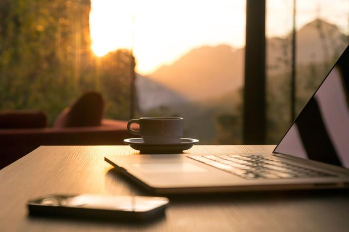 A laptop, smartphone, and cup of coffee sitting on a table overlooking a bank of windows.