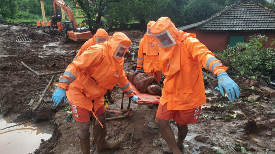 This photograph provided by India's National Disaster Response Force (NDRF) shows NDRF personnel recovering the body of a landslide victim at Ratnagiri in the western Indian state of Maharashtra, Sunday, July 25, 2021. Officials say landslides and flooding triggered by heavy monsoon rain have killed more than 100 people in western India. (National Disaster Response Force via AP)