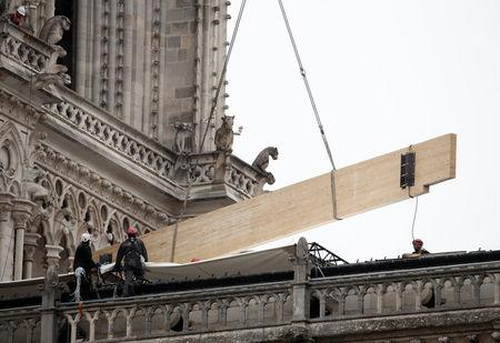 Workers install temporary tarpaulins to protect Notre-Dame Cathedral from rain damage, a week after a massive fire devastated large parts of the gothic structure in Paris, France, April 23, 2019.  REUTERS/Benoit Tessier